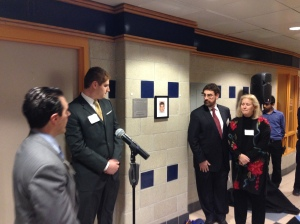 Dean Konwerski, Jared Smith, Dr. Matthew Smith, and Rhonda Smith unveil the new plaque outside the Steven E. Smith Broadcasting Center